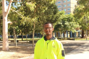 a man in a hi-vis jacket in front of the camera with a large open park behind him
